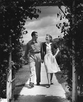 hulton archive/couple outdoors holding hands walking
