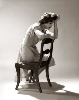 Depressed Sad Moody Woman Leaning Head Onto Arm Slouched Lean Back Of Chair Seated