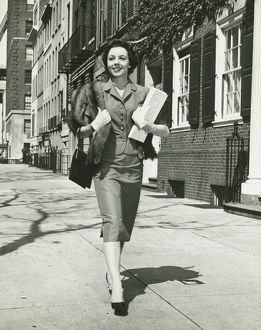 Elegant woman walking on sidewalk, holding bags, (B&W)
