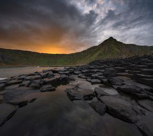 Giant's Causeway with colorful sunrise looking towards the cliffs