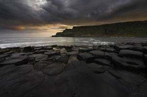 Giant's Causeway on moody morning with colorful sunrise