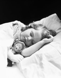 Girl sleeping, head on pillow, baby doll toy under arm.
