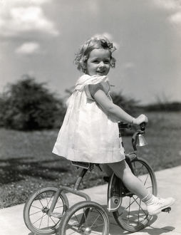 Girl wearing summer dress, riding tricycle down sidewalk