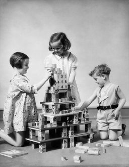 Two girls and one boy playing with alphabet building blocks constructing multi story