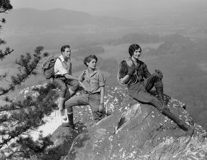 Group of three climbers atop mountain.