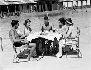 Group of people sitting poolside at hotel, eating dinner, Miami, Florida.