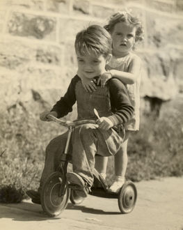 hulton archive/little boy giving little girl ride tricycle
