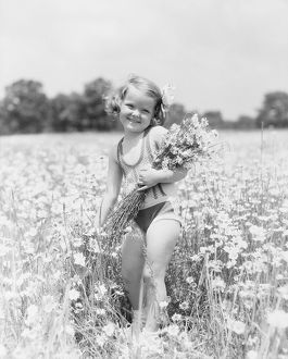 Little girl picking daisy bouquet in summer meadow.