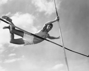 Male pole-vaulter clearing bar