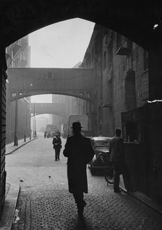 A man in a bowler hat walking under the arches on the cobbled Wapping High Street, London