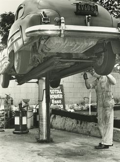 Man repairing uplifted car, (B&W), low section