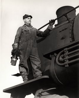 Man standing on train engine, holding oil can.