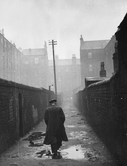 A man walking through a backstreet of the Gorbals area of Glasgow