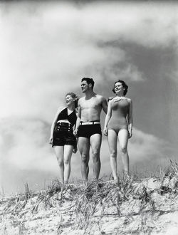 Man and two women standing on beach sand dune.