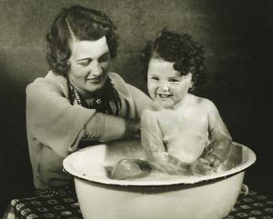 Mother bathing daughter (12-18 months) in basin, (B&W)