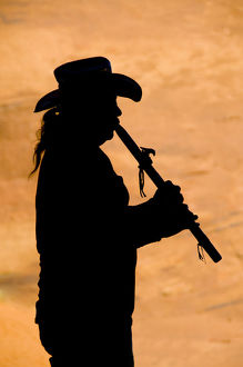 Navajo in silhouette playing flute
