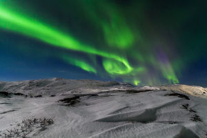 Northern lights over the snow-capped mountains