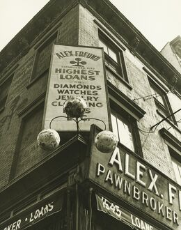 Pawnbroker sign on building corner, (B&W), low angle view
