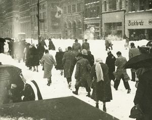 People walking on city street in blizzard, (Rear view)