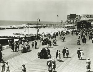 People walking on promenade by seashore, (B&W), (Elevated view)