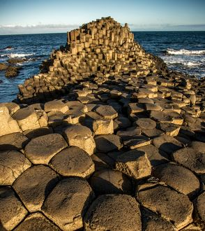 The rising sun on a rock formation called the Giant's Causeway, County Antrim