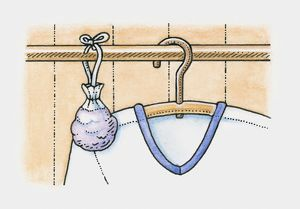 Sachet of lavender hanging on clothes rail in wardrobe, next to a shirt