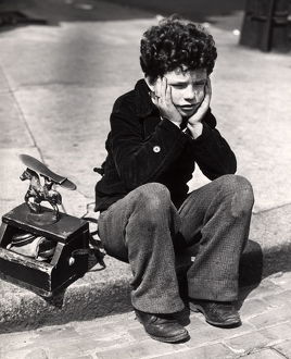 Sad Boy, Curly Hair Sitting On Curb Patched Trousers Shoeshine Kit Work Working Worker