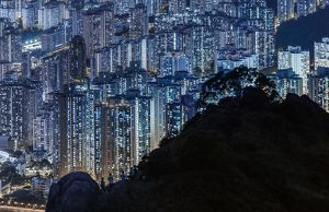 Silhouette of mountain over illuminated Hong Kong