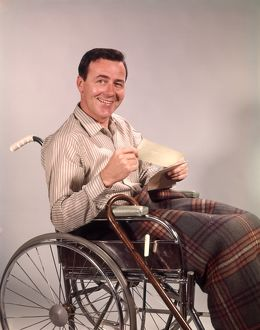 Smiling man in wheelchair, holding insurance check.