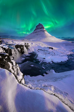 Spectacular northern lights appear over Mount Kirkjufell and waterfall in Iceland.
