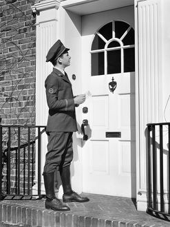 Teenage messenger boy delivering message at front door.