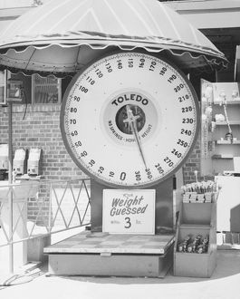 Weighing scale at amusement park, (B&W)
