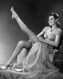 Woman in evening wear pullin on silk stockings