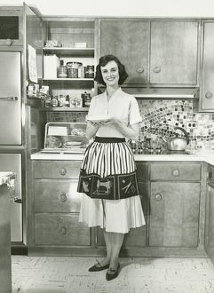 Woman holding pie, posing in kitchen, (B&W), portrait