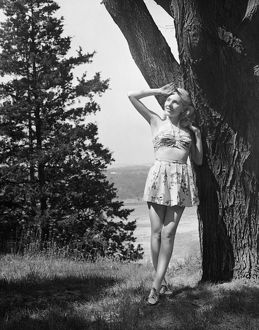 hulton archive/woman leaning tree