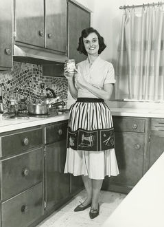 Woman posing in kitchen, (B&W), portrait