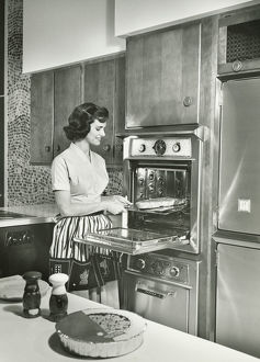 Woman putting meal into oven in kitchen, (B&W),