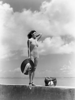 Woman Wearing Knit Bathing Suit Standing Wall Ocean Sea Background Holding Sun Hat