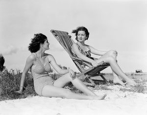 Two women in bathing suits on windy beach.