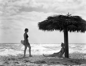 Two women under palm thatch umbrella on beach, Florida.