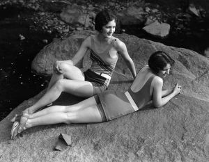 Two women relaxing on rock, by creek. (Photo by H