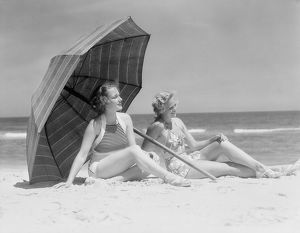 Two women sitting on beach under parasol.