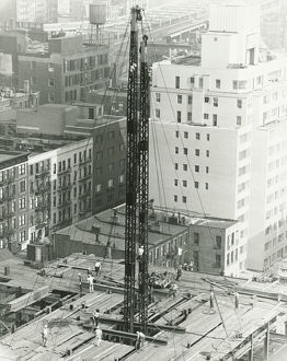 Workers on building site on urban setting, (B&W), elevated view