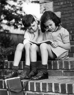 hulton archive/young boy girl reading book outdoors