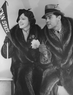 Young couple in fur coats sitting, facing same direction, (B&W),