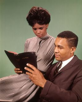 Young couple reading bible.