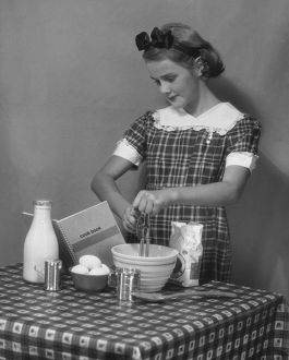 hulton archive/young woman preparing food