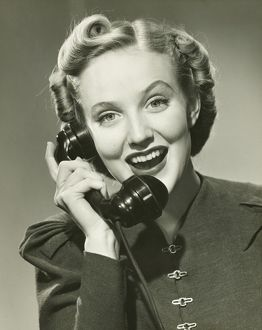Young woman using phone, smiling, (B&W), portrait